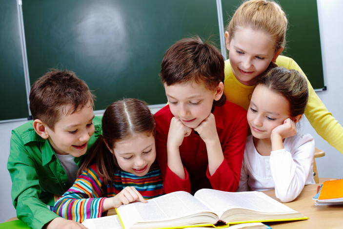 group of happy kids reading a book together