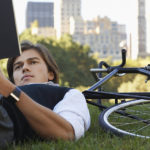man reading a book in the park next to bicycle on work break